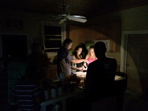 The expat Americans of Eleuthera gather by the glow of cell phones and flashlights for Thanksgiving dinner.