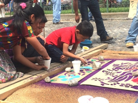 Children help their parents with the family alfombra