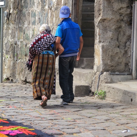 An elderly Mayan woman is helped down the street by her grandson